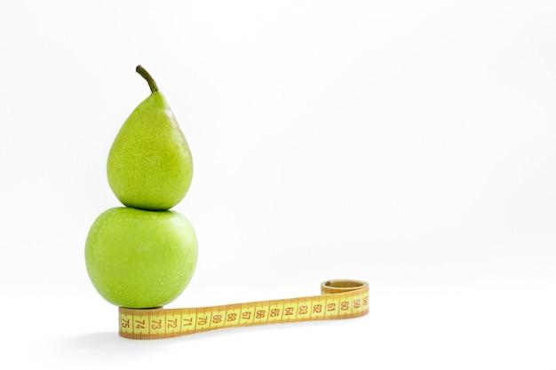 Un centimètre, une pomme et une poire verte sur un fond blanc