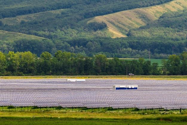 Centrale solaire sur fond de collines verdoyantes.