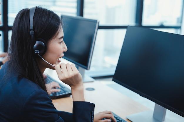Centre d'appel femme conseillant les clients appelant.
