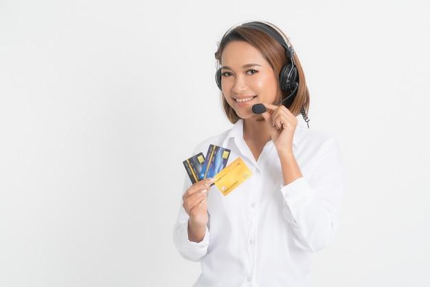 Centre d'appels femme avec casque et carte de crédit.