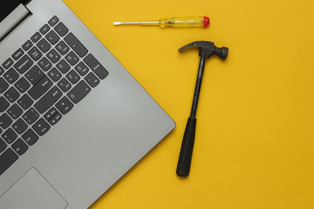 Centre de service réparation ordinateur portable tournevis et marteau pour ordinateur portable sur fond jaune