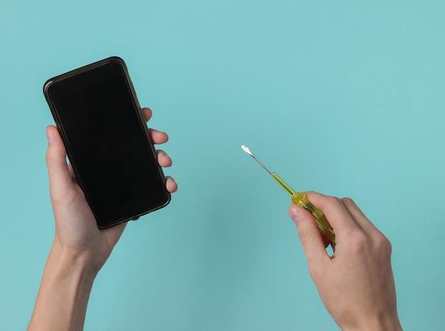 Centre de service réparation de smartphone main féminine tient un tournevis et un smartphone