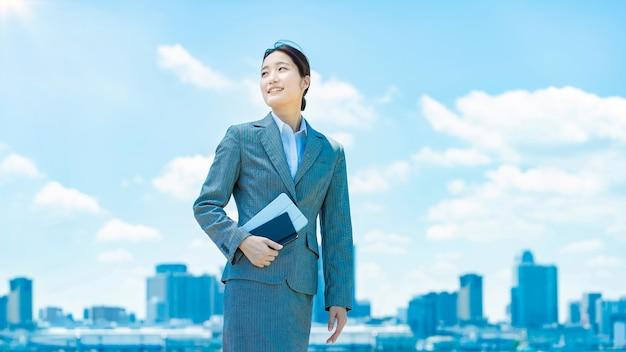 Centre-ville, ciel bleu et jeune femme d'affaires asiatique