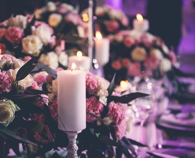 Centres floraux avec des bougies enflammées