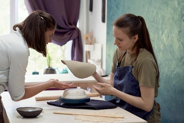 Céramiste enseignante aux jeunes étudiants en formation et moulage en atelier