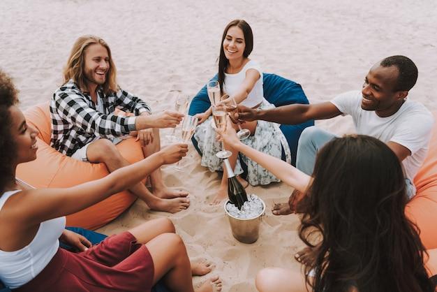 Cercle d'amis en liesse sur la plage de sable
