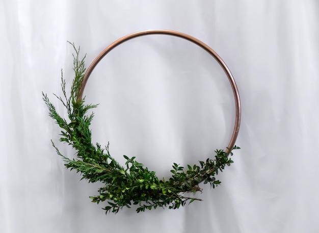 Cercle de bronze avec des buis verts et arbre de noël sur blanc