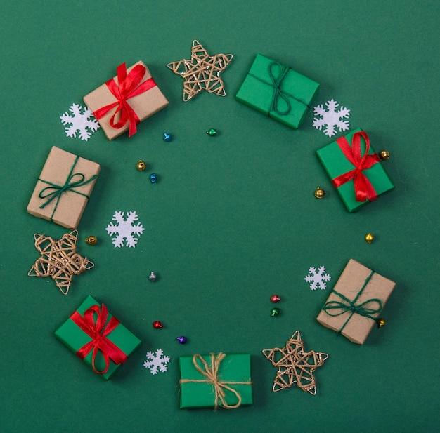 Cercle composé de cadeaux de noël, d'étoiles et de flocons de neige, sur fond vert