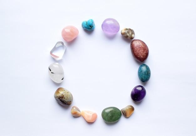 Le cercle est tapissé de minéraux naturels. pierres semi-précieuses de différentes couleurs, brutes et travaillées. améthyste, quartz rose, agate, apatite, aventurine sur fond blanc.