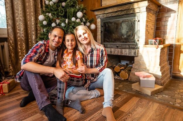 Cercle de famille à thème noël et nouvel an. jeune famille caucasienne assise sur un plancher en bois à la maison dans le salon près de l'arbre de noël de la cheminée.