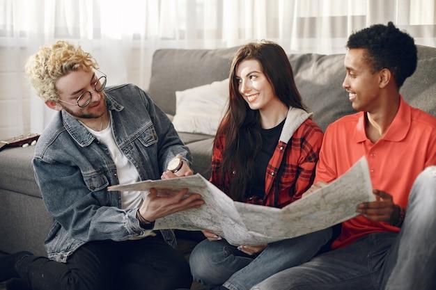 Cercle heureux d'amis planifiant un voyage. globe-trotters inspectant une carte étant à la maison. ethnie européenne et indienne.