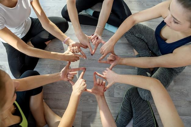 Cercle de mains humaines faisant des exercices de yoga se bouchent