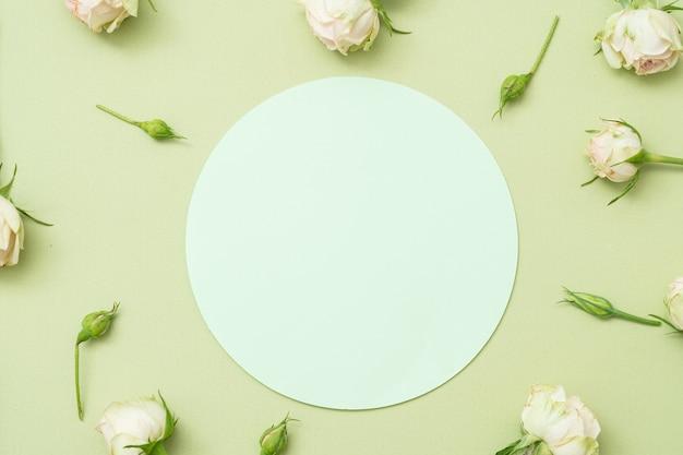 Cercle de papier vierge sur fond vert. décor de fleurs.