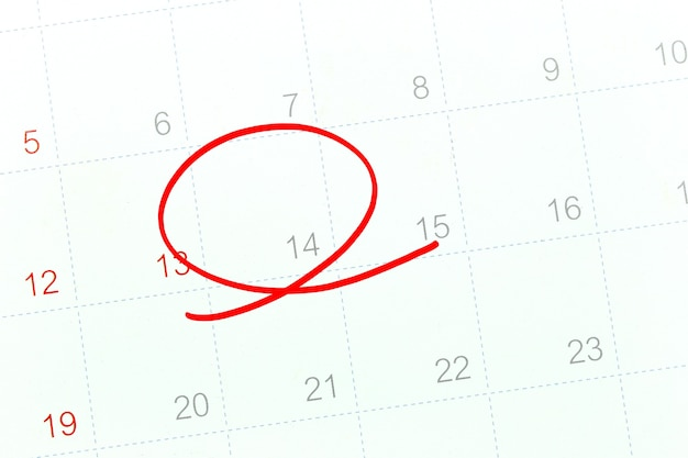 Le cercle rouge du stylo sur le papier calendrier montre le 14 pour la conception dans le concept de la saint-valentin.