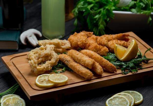 Cercles d'oignons et bâtonnets de poulet grillés servis avec des tranches de citron