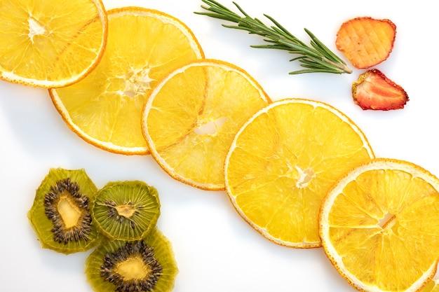 Cercles de tranches de kiwi orange séché et de fraise sur fond blanc