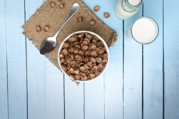 Céréales et bouteille de lait et verre de lait sur une table en bois blanche.