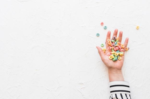 Céréales colorées sur la main de femme d'affaires sur fond texturé blanc