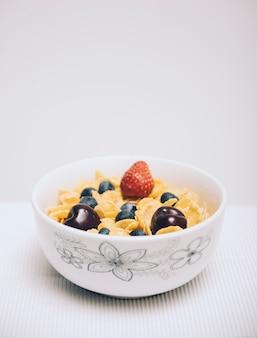 Céréales cornflake avec des baies dans un bol sur fond blanc