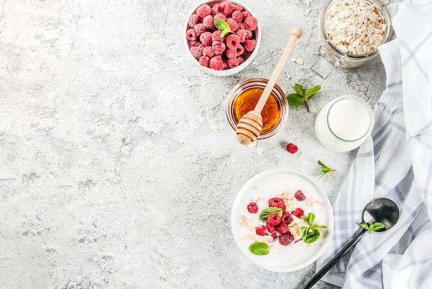 Céréales, framboise fraîche, feuilles de menthe, yaourt et miel
