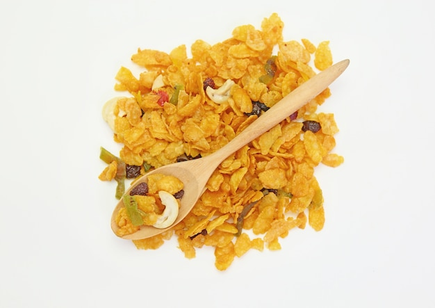 Céréales avec des fruits secs dans une cuillère en bois contre les céréales sur fond blanc