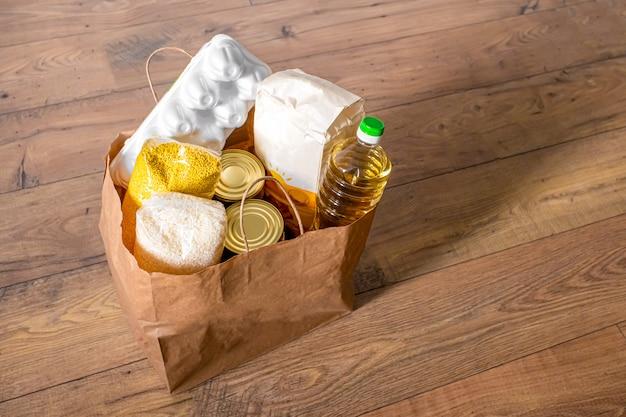 Céréales, grains, huile, ragoût, bouillie et épicerie en conserve dans un sac d'artisanat pour les achats.