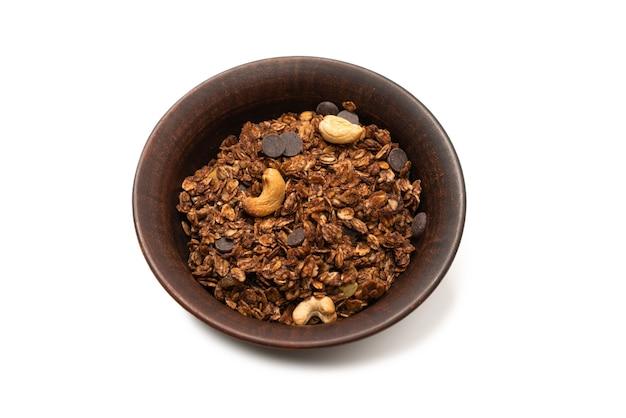 Céréales granola au chocolat avec des noix dans un bol en arrière-plan. isolé sur bacckground blanc.
