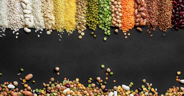 Céréales et légumineuses colorées séchées sur fond texturé noir. vue de dessus, copiez l'espace.