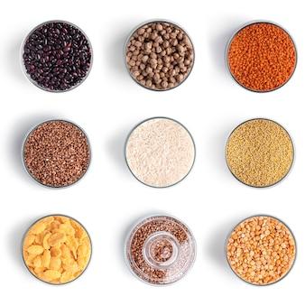 Céréales et légumineuses en pots sur mur blanc.