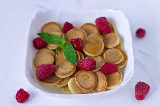 Céréales de mini crêpes aux framboises et une feuille de menthe dans une assiette blanche