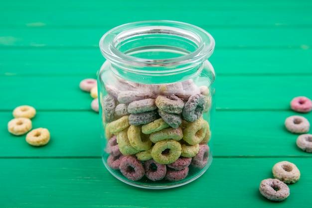 Céréales multicolores sur un bocal en verre avec des céréales isolées sur une surface verte
