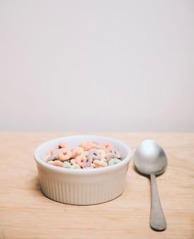 Céréales multicolores dans le bol blanc et une cuillère sur un bureau en bois sur fond blanc