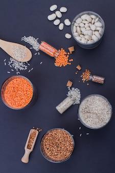 Céréales non cuites à plat et récipients en verre avec des cuillères en bois. vue de dessus collectée lentilles riz sarrasin et haricots blancs sur fond bleu.