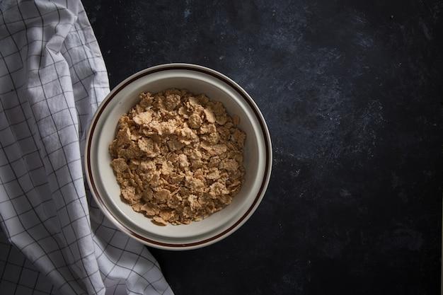 Céréales de petit-déjeuner au son de blé sans lait dans un bol. fond noir avec serviette de table.