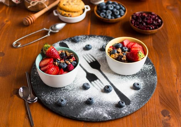 Céréales, petit-déjeuner avec muesli et fruits frais dans des bols sur une table en bois rustique