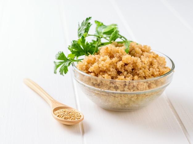 Céréales de quinoa dans un bol en verre sur une table en bois blanche avec des feuilles de persil.