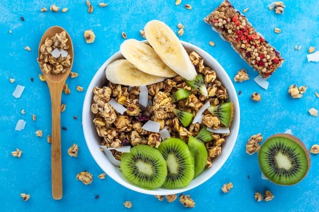 Céréales sèches pour le petit-déjeuner. bol de muesli croustillant au miel avec des tranches de banane fraîche et du kiwi sur fond bleu. alimentation saine, en forme et en fibres. vue de dessus. l'heure du déjeuner