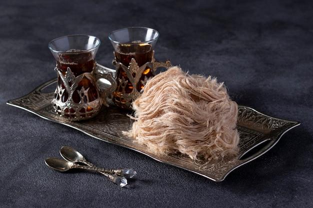 Cérémonie du thé avec barbe à papa turque pismaniye sur plateau en métal vintage sur fond gris foncé.
