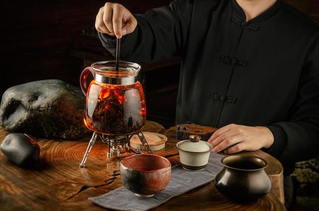 La cérémonie du thé infusant du thé en feu dans une théière en verre