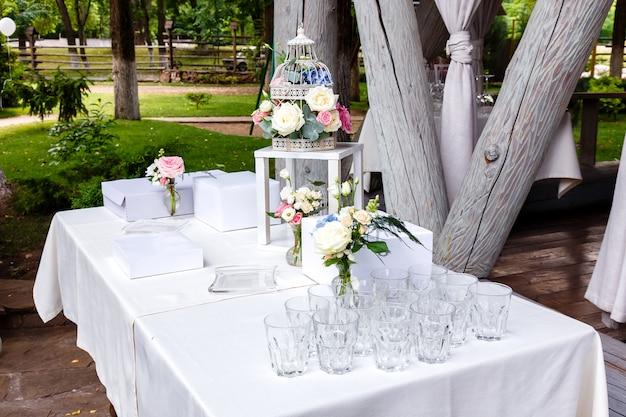 Cérémonie de mariage, bouquets de roses, verres au restaurant en plein air.