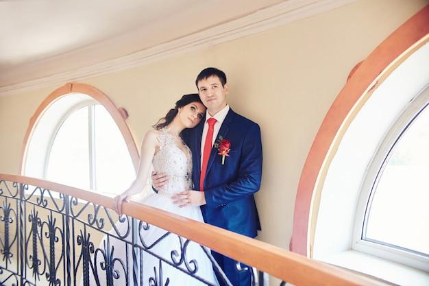 Cérémonie de mariage dans l'ancien homestead. jeunes mariés étreignant et debout dans les escaliers. organisateur de mariage