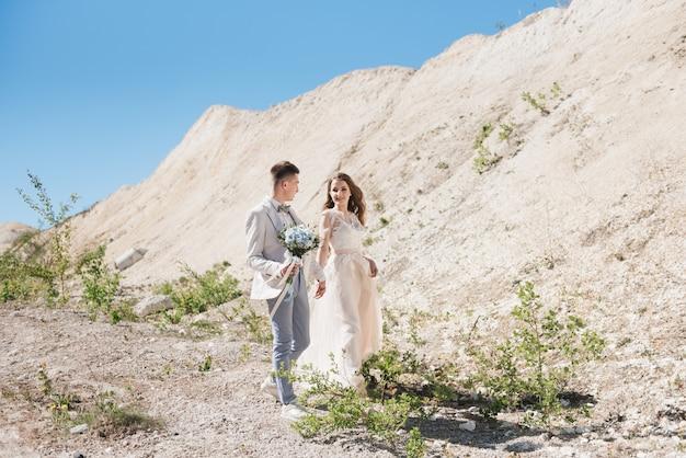 Cérémonie de mariage dans les montagnes. la mariée et le marié debout devant les montagnes de sable. le couple heureux, un beau mariage dans un endroit pittoresque