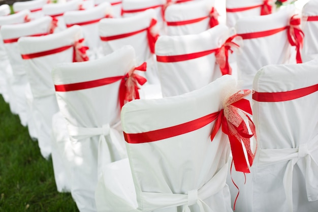 Cérémonie de mariage à l'extérieur. chaises blanches avec ruban rouge.