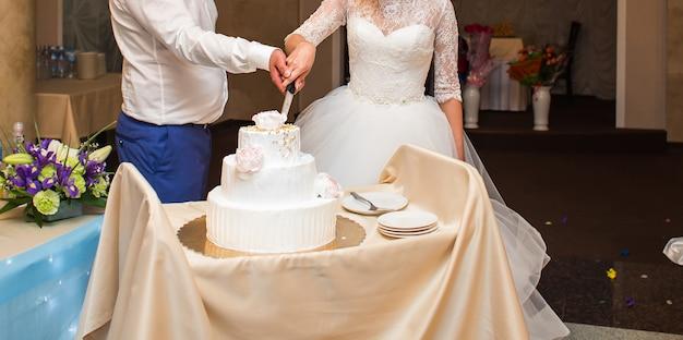 Cérémonie de mariage. gâteau de coupe des mariés.