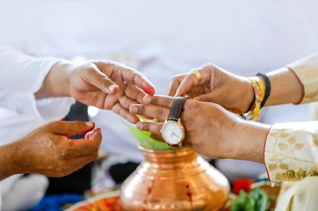 Cérémonie de mariage indien traditionnel, regarder à la main du marié
