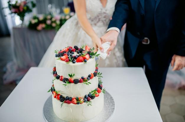 Cérémonie de mariage. mains de jeunes mariés coupent un gâteau blanc à trois niveaux avec des fraises et des mûres