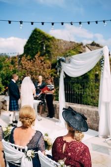 Cérémonie de mariage avec une mariée vêtue d'une robe de mariée, un marié vêtu d'une robe nationale écossaise et des invités en