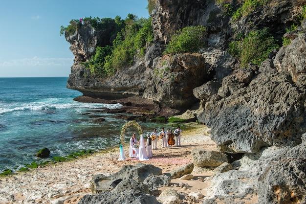 Cérémonie de mariage sur la plage au coucher du soleil avec des musiciens