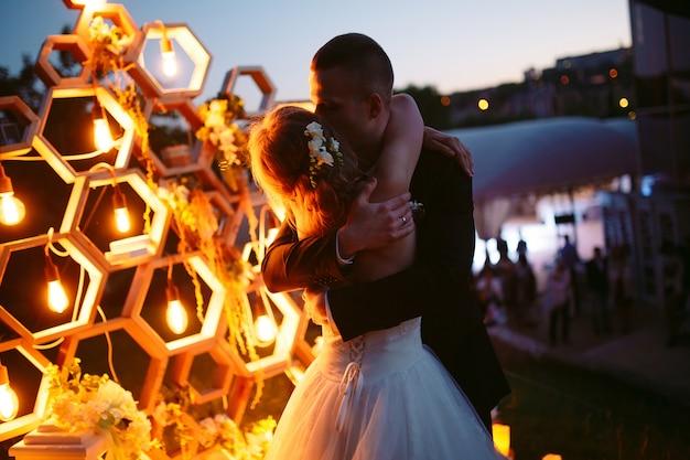 Cérémonie de mariage en soirée. la mariée et le marié sont à l'arrière-plan de l'arc de mariage.