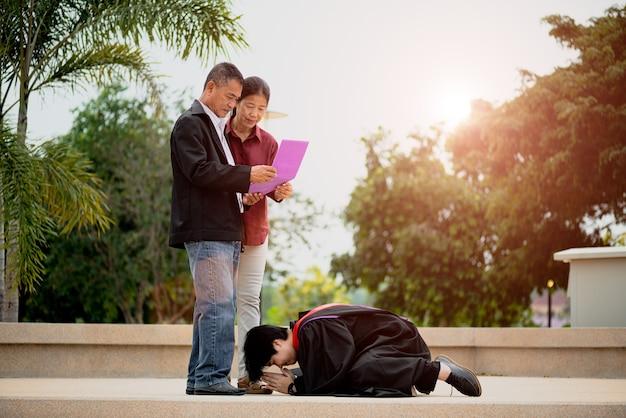 Cérémonie de remise des diplômes. femme diplômée donnant un certificat de fin d'études à ses parents